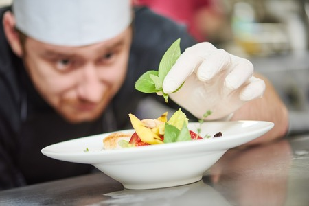 chef kitchen: male cook chef decorating garnishing prepared salad dish on the plate in restaurant commercial kitchen Stock Photo