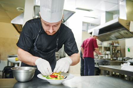 hotel kitchen: male cook chef decorating garnishing prepared salad dish on the plate in restaurant commercial kitchen Stock Photo