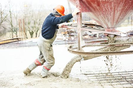 saltar: Trabajos de hormigonado. sitio de construcción trabajador durante el vertido del hormigón en un encofrado en el área de salto con la construcción de barril Foto de archivo