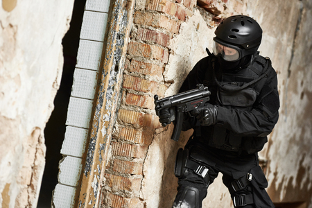 special agent: Military industry. Special forces or anti-terrorist police soldier, private military contractor armed with machine gun ready to attack during clean-up operation