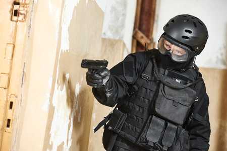 police unit: Military industry. Special forces or anti-terrorist police soldier armed with pistol ready to attack during clean-up operation Stock Photo