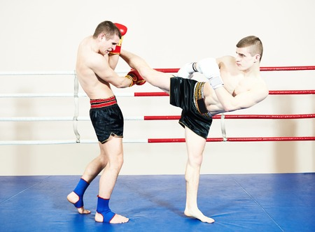 elbow pad: Two male muay thai boxers fighting at training boxing ring