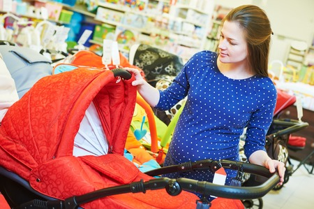 shopping buggy: Pregnancy shopping. Pregnant woman choosing pram for newborn carriage at baby shop store