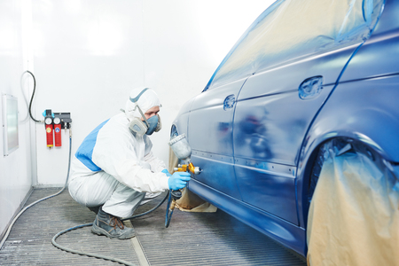 automobile repairman painter in protective workwear and respirator painting car body bumper in paint chamber Stockfoto