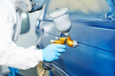 automobilový opravář malíř ruku v ochranné rukavice s airbrush pistole malba karoserii v barvě komoře