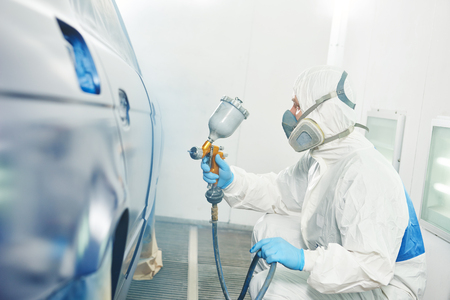 painter: automobile repairman painter in protective workwear and respirator painting car body in paint chamber Stock Photo