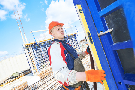 rigger: Male construction builder worker with bubble level at building site Stock Photo