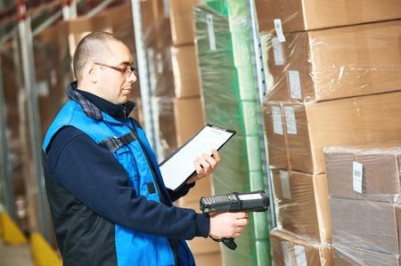 registros contables: paquete de exploración Trabajador de sexo masculino con un escáner de código de barras en el almacén moderno