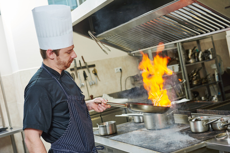 cocinero: Preparación de comida. Cocinero en la cocina del restaurante con la cacerola sobre la estufa haciendo flameados