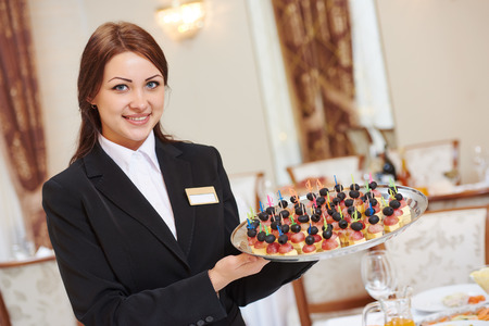 hotel service: Restaurant catering services. Waitress with food dish serving banquet table