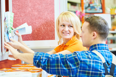 merchandiser: Sales assistant at work. smiling female hardware store worker helps to choose paint for painting to buyer customer with color samles during shopping