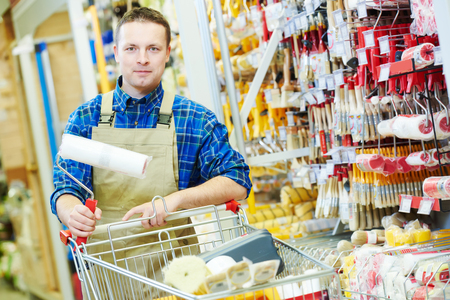 retail shopping: happy hardware store worker or painter buyer customer with shopping cart looking at the camera