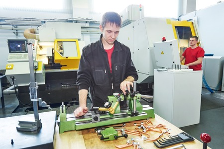 measuring instruments: Metalwork. Male worker in uniform checking quality of processed tool using precise optical device