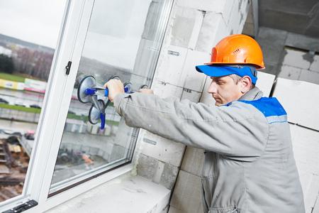 männlich Industrie Baumeister Arbeiter bei Einbau von Fenstern in der Baustelle Bau Standard-Bild