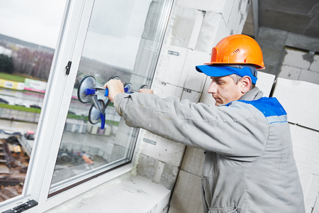 window panes: male industrial builder worker at window installation in building construction site Stock Photo