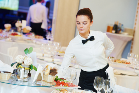 food service occupation: waitress occupation. Young woman with food on dishes servicing in restaurant during catering the event