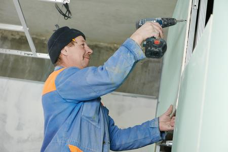 carpintero: Carpintero ebanista escayolista con un destornillador sistema de montaje de placas de yeso laminado Foto de archivo