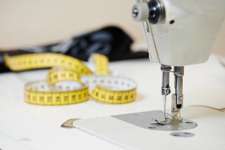 sartorial: tailoring equipment. sewing machine with measure tape