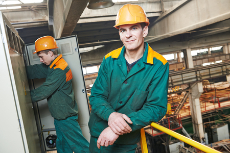 screwing: young adult electrician builder engineer in front of his co-worker screwing equipment in fuseboard Stock Photo