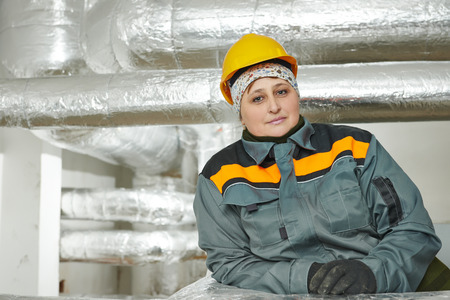 fibreglass: Thermal insulation. Female insulation worker in front of isolated by glass wool and foil industrial pipes
