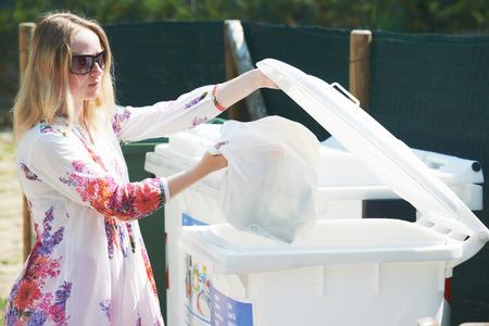 separacion de basura: Reciclaje - la separación de basura. Mujer tirando de plástico vacía en la basura