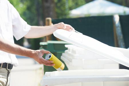 separacion de basura: separación de la basura. Hombre mano tirando de lata vacía del metal en la basura