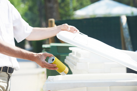 separacion de basura: separaci�n de la basura. Hombre mano tirando de lata vac�a del metal en la basura