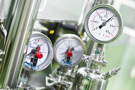 Gros plan de manomètre, tuyaux et de robinets de chauffage dans une chaufferie