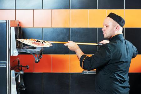 competencias laborales: cocinero del panadero del cocinero con el uniforme negro que pone la pizza en el horno con la pala en la cocina de un restaurante
