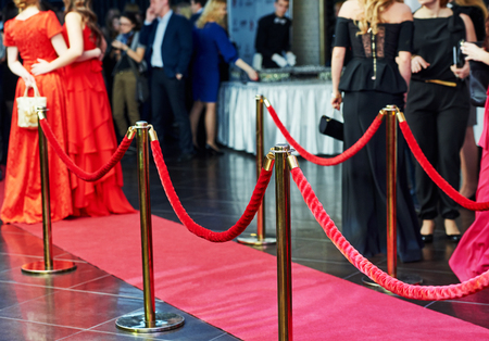 stanchion: event party. red carpet entrance with golden stanchions and ropes. guests in the background