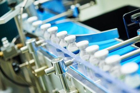 製薬業界。工場でガラス瓶アンプルの生産ライン機械コンベア