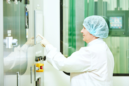 setup operator: pharmaceutical factory woman worker operating production line at pharmacy industry manufacture factory Stock Photo