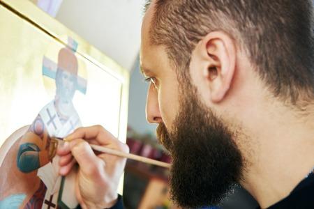 madre trabajando: Religiosa hombre icono pintor pinta un nuevo icono con el cepillo en el taller Foto de archivo
