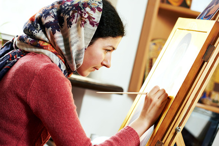 iconography: Iconography. Religious icon painter woman paints a new icon with brush at workshop Stock Photo