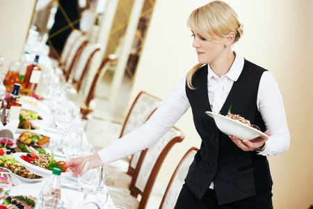 banquet table: Restaurant catering services. Waitress serving banquet table Stock Photo