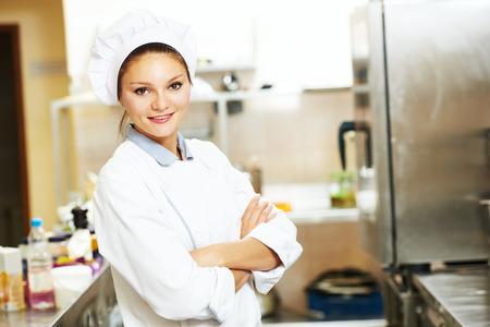 Female chef portrait  in white uniform in hotel or restaurant kitchen