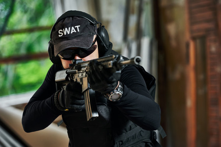 private security: military industry. Portrait of special forces or anti-terrorist police soldier, private contractor armed with assault rifle ready to attack during clean-up operation, mission Stock Photo