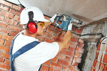 drill: Builder worker with pneumatic hammer drill perforator equipment making hole in wall at construction site Stock Photo