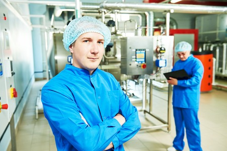 Two pharmaceutical technician male workers operating water preparation production line at pharmacy industry manufacture factory using notebook computer Archivio Fotografico