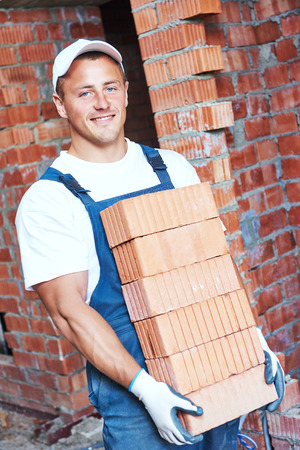 masonry: Construction worker. Mason bricklayer carrying a heavy load of red bricks