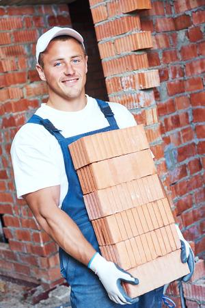 carga: Obrero. Mason albañil que lleva una pesada carga de ladrillos rojos