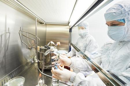 female-Science-Forscher in der schützenden Uniform und Ausrüstung arbeitet mit gefährlichen Gefährdungsvirusmaterial auf mikrobiologische Labor Lizenzfreie Bilder