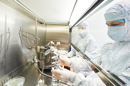 vacuna: investigadores de ciencias de mujeres en uniforme y equipo de protecci�n trabaja con material de virus en el laboratorio peligro peligroso Microbiolog�a- Foto de archivo