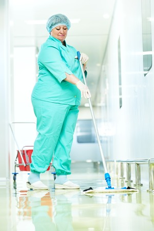 bioclean: Adult cleaner woman in uniform with mop cleaning corridor pass floor of pharmacy industry factory or medical clinic