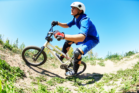 uphill: Extreme sport concept. Young cyclist riding the mountain bike uphill or cross-country course