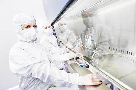 peligro: investigadores de ciencias de mujeres en uniforme y equipo de protecci�n trabaja con material de virus en el laboratorio peligro peligroso Microbiolog�a- Foto de archivo