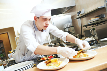 young male cook chef in white uniform decorating food on the plate in restaurant commercial kitchen