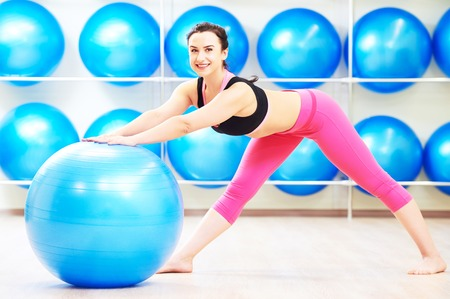 warm up exercise: beautiful smiling woman  doing warm up exercise with fitness ball for balance in sport club