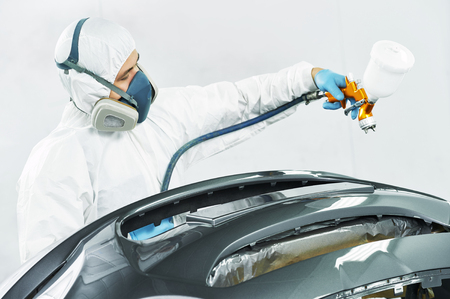 priming paint: auto mechanic worker painting auto car bumper in a paint chamber during repair work Stock Photo