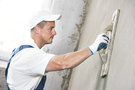 parget: Male plasterer at indoor wall renovation decoration with putty knife float Stock Photo